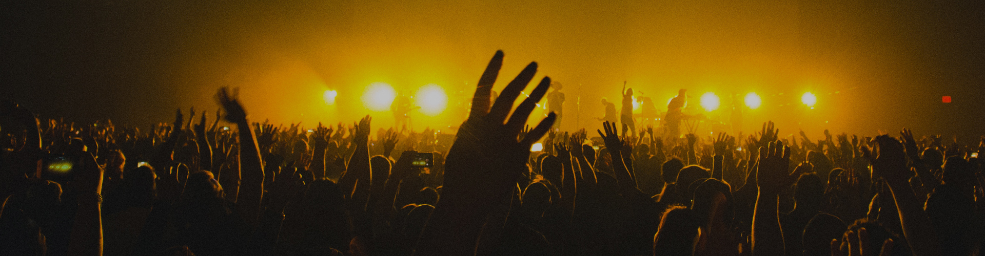 Hundreds of people with hands lifted at a concert.